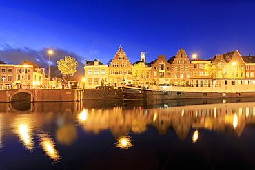 Dusk lights on typical houses and bridge reflected in a canal of the River Spaarne, Haarlem, North Holland, The Netherlands, Europe