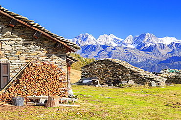 Alpine huts framed by snowy peaks of Bernina Group, Arcoglio Alp, Val Torreggio, Malenco Valley, Valtellina, Lombardy, Italy, Europe