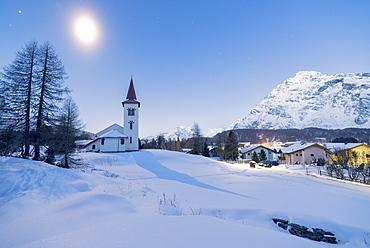 Lights of dusk on Chiesa Bianca and alpine village covered with snow, Maloja Pass, Engadine, Canton of Graubunden, Switzerland, Europe