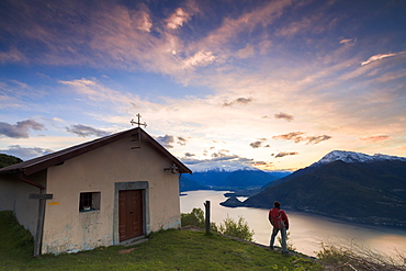 Hiker at the church of San Domenico admires Lake Como framed by pink sky at dawn, Cremia, Lombardy, Italian Lakes, Italy, Europe
