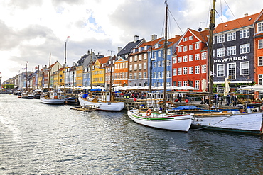 Colourful facades and typical boats along the canal and entertainment district of Nyhavn, Copenhagen, Denmark, Europe