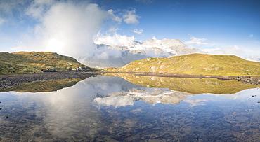 Panoramic of mountain peaks reflected in lake, Bernina Pass, Poschiavo Valley, Engadine, Canton of Graubunden, Switzerland, Europe