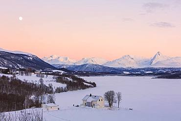 Sunrise on typical house with Lyngen Alps in the background, Mestervik, Troms county, Norway, Scandinavia, Europe