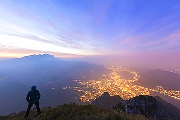 Hiker on Monte Coltignone looks toward Monte Resegone and Lecco at dawn, Lombardy, Italian Alps, Italy, Europe