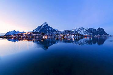 Overview of village and snowy peaks at dusk, Reine Bay, Lofoten Islands, Nordland, Norway, Europe