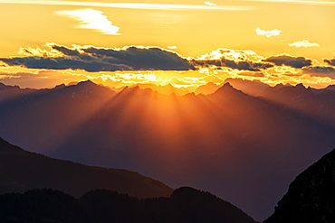 Sun rays at sunset on Pizzo Berro and Gerola Valley seen from San Marco Pass, Orobie Alps, Bergamo province, Lombardy, Italy, Europe