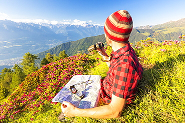 Hiker with map and binoculars looks towards Rhaetian Alps and Monte Disgrazia from Pizzo Berro, Bitto Valley, Lombardy, Italy, Europe