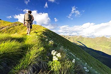 Hiker on steep ridge on the ascent towards Monte Azzarini, San Marco Pass, Albaredo Valley, Orobie Alps, Lombardy, Italy, Europe