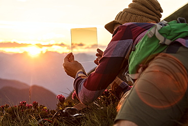 Man at sunset with graduated photography filters in his hand, San Marco Pass, Orobie Alps, Bergamo province, Lombardy, Italy, Europe