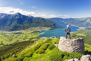 Hiker on top of Monte Berlinghera looks towards Colico and Monte Legnone, Sondrio province, Lombardy, Italy, Europe