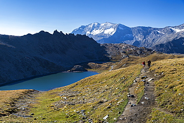 Hikers walking on the Colle del Nivolet beside Rossett Lake (Lago Rossett), Gran Paradiso National Park, Alpi Graie (Graian Alps), Italy, Europe