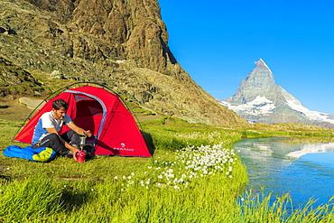 Hiker at lake Riffelsee makes coffee outside tent facing the Matterhorn, Zermatt, canton of Valais, Swiss Alps, Switzerland, Europe