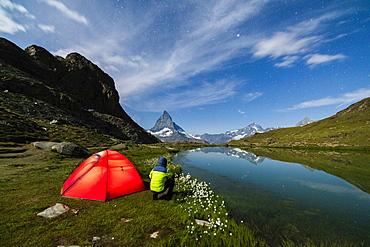 Hiker beside tent looking towards the Matterhorn from lake Riffelsee, Zermatt, canton of Valais, Swiss Alps, Switzerland, Europe
