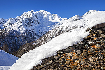 Stone hut covered with snow with Monte Disgrazia on background, Alpe dell'Oro, Valmalenco, Valtellina, Lombardy, Italy, Europe