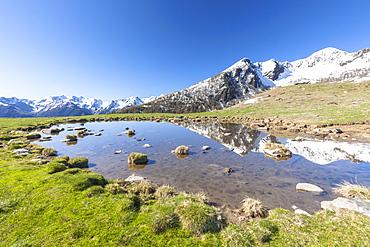 Snowy peaks reflected in the alpine lake, Motta di Olano, Valgerola, Valtellina, Sondrio province, Lombardy, Italy, Europe