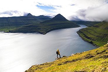 Hiker on rocks looks at the fjords, Funningur, Eysturoy island, Faroe Islands, Denmark, Europe