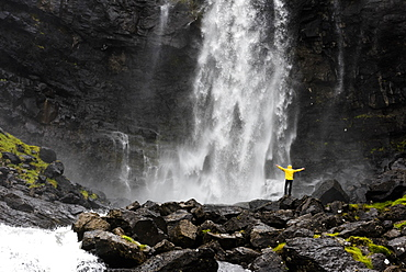 Hiker at Fossa waterfall, Streymoy island, Faroe Islands, Denmark, Europe