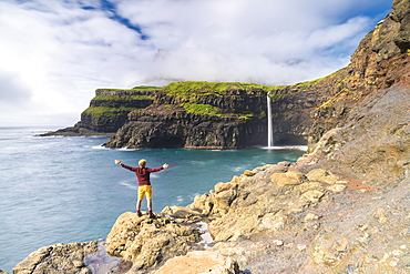 Man on cliffs with open arms admiring Gasadalur waterfall, Vagar island, Faroe Islands, Denmark, Europe