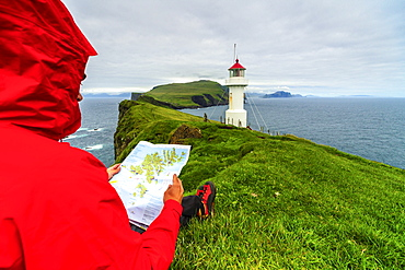 Hiker on cliffs looks at the map next to lighthouse, Mykines island, Faroe Islands, Denmark, Europe