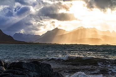 Sun rays above the rough sea of Flakstadoya seen from Vareid, Nordland, Lofoten Islands, Norway, Europe