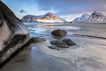 Sunset on the surreal Skagsanden beach surrounded by snow covered mountains, Flakstad, Lofoten Islands, Arctic, Norway, Scandinavia, Europe