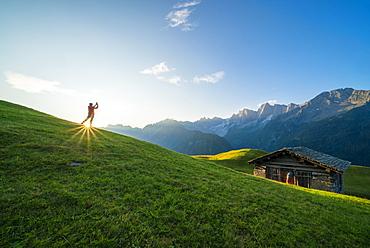 Man lit by the sunburst photographing Piz Badile and Cengalo, Tombal, Soglio, Val Bregaglia, canton of Graubunden, Switzerland, Europe