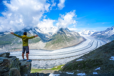 Man exulting with outstretched arms looking at Aletsch Glacier from Eggishorn viewpoint, Bernese Alps, canton of Valais, Switzerland, Europe