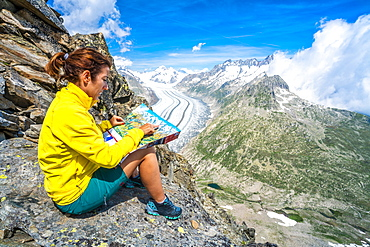 Woman looking at map sitting on rocks at Eggishorn viewpoint above Aletsch Glacier, Bernese Alps, canton of Valais, Switzerland, Europe