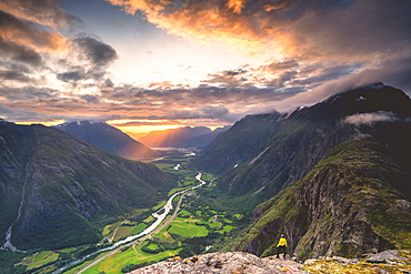 Elevated view of man standing on Romsdalseggen ridge admiring Rauma valley during sunset, Andalsnes, More og Romsdal, Norway, Scandinavia, Europe
