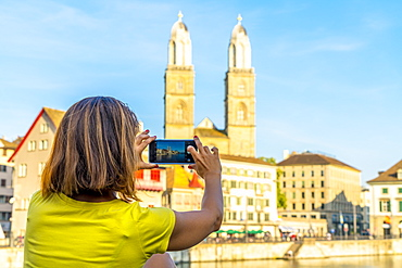Rear view of woman photographing Grossmunster Cathedral and Limmat River with smartphone, Zurich, Switzerland, Europe