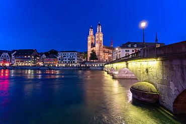 Illuminated buildings of Limmatquai and Grossmunster at dusk from Munsterbrucke bridge, Zurich, Switzerland, Europe
