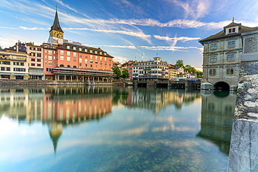 St. Peter church and old buildings of Lindenhof mirrored in Limmat River at dawn, Zurich, Switzerland, Europe