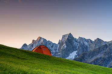 Sunrise lights over a tent overlooking Piz Badile and Cengalo, Tombal, Soglio, Val Bregaglia, Canton of Graubunden, Switzerland, Europe