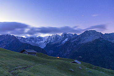 Stars over tent and huts overlooking Piz Badile and Piz Cengalo, Tombal, Soglio, Valbregaglia, Canton of Graubunden, Switzerland, Europe