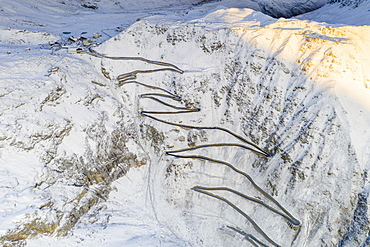 Narrow bends of the Stelvio Pass road on steep snowy mountain ridge, aerial view by drone, Bolzano province, South Tyrol side, Italy, Europe