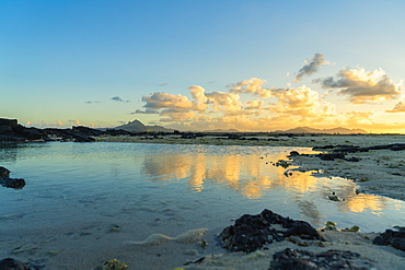 Clouds mirrored in the calm water of the Indian Ocean at sunset, Trou d'Eau Douce, Flacq district, East coast, Mauritius, Africa