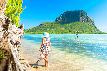 Woman on tropical beach looking at paddleboard in the lagoon, La Gaulette, Le Morne Brabant, Black River, Mauritius, Indian Ocean, Africa