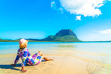 Woman in bright dress relaxing on tropical beach, La Gaulette, Le Morne Brabant, Mauritius, Indian Ocean, Africa