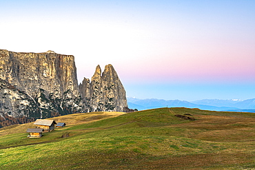 Autumn sunrise over Sciliar peaks and wood huts at Alpe di Siusi (Seiser Alm), Dolomites, South Tyrol, Italy, Europe