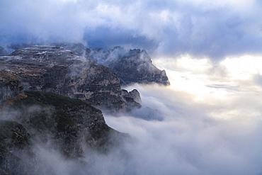 Sunlight over Croda dei Toni through the autumn fog covering Auronzo Valley, Sesto Dolomites, Trentino-Alto Adige/Veneto, Italy, Europe