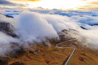 Aerial view by drone of fog over scenic road crossing Giau Pass in a sea of clouds at sunset, Dolomites, Belluno province, Veneto, Italy, Europe
