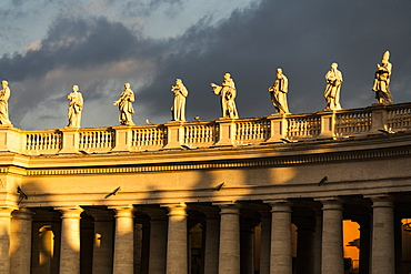 Statues of St. Peter's Square colonnade lit by sunrise, Vatican City, UNESCO World Heritage Site, Rome, Lazio, Italy, Europe