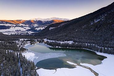 Sunrise over the village of Dobbiaco and frozen lake, Val Pusteria, Dolomites, Bolzano province, South Tyrol, Italy, Europe