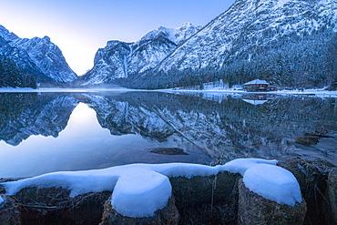 Winter dusk over Lake Dobbiaco surrounded by snow, Dobbiaco, Val Pusteria, Dolomites, Bolzano province, South Tyrol, Italy, Europe