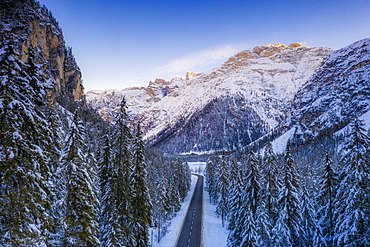 Aerial view by drone of sunrise on the scenic road Dobbiaco-Misurina along snowy woods, Dolomites, South Tyrol, Italy, Europe
