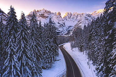 Aerial view by drone of car traveling on the scenic road Dobbiaco-Misurina along snowy woods at dawn, Dolomites, South Tyrol, Italy, Europe