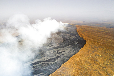 Arid soil on edge of the smoky Erta Ale volcano from above, Danakil Depression, Afar Region, Ethiopia, Africa
