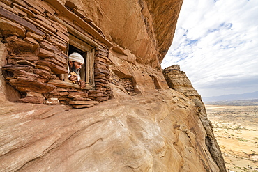 Priest looking out from a small window carved into rocks in Abuna Yemata Guh church, Gheralta Mountains, Tigray Region, Ethiopia, Africa