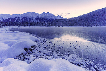 Sunrise over the frozen lake Lej da Staz and snowy woods, St. Moritz, Engadine, canton of Graubunden, Switzerland, Europe