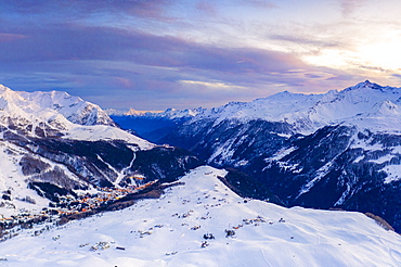Aerial view by drone of sunset on the snowy peaks surrounding Madesimo and Andossi, Valchiavenna, Valtellina, Lombardy, Italy, Europe